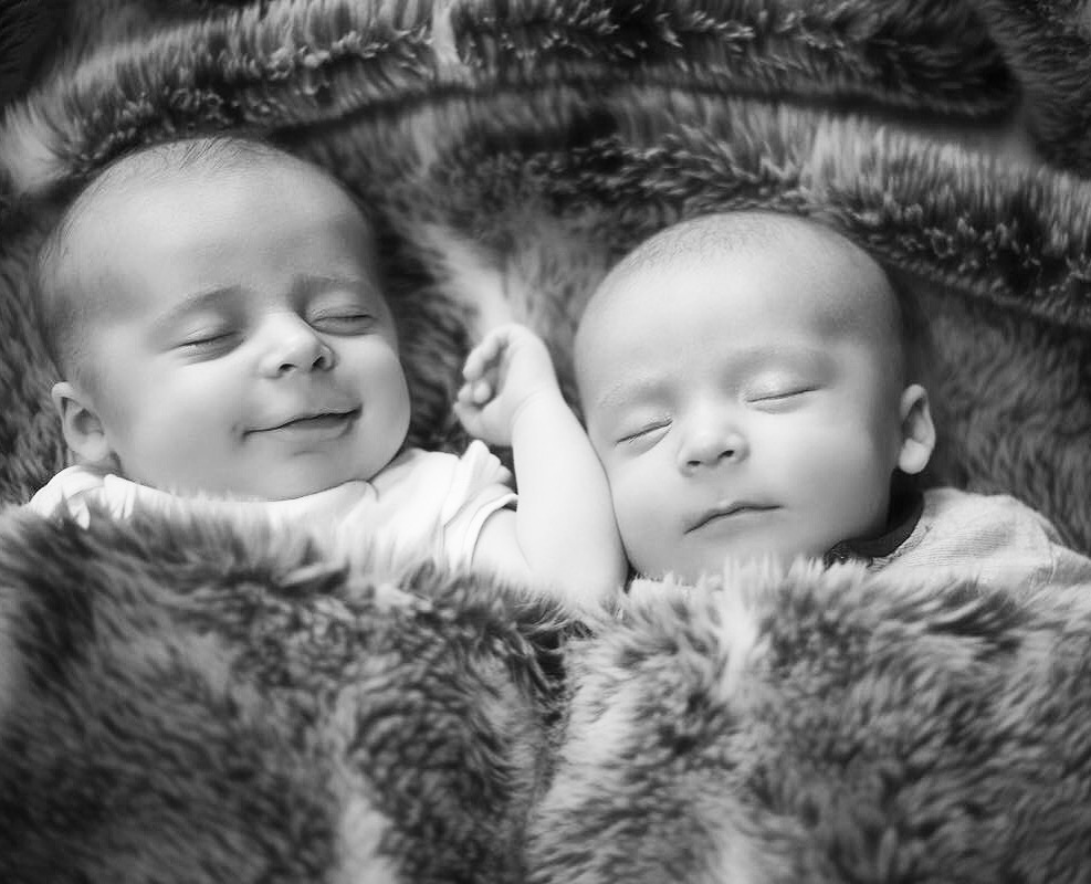Twin baby boys sleeping next to each other