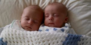 Small twin babies sleeping next to each other