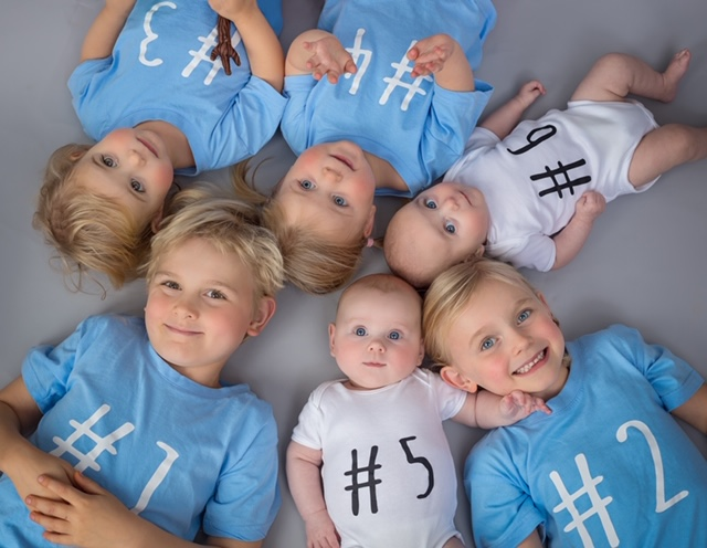x6 children laying on floor with numbered tops on, x2 sets of twins